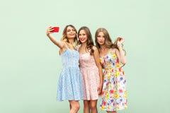Tres hermanas hermosas en el vestido, selfie macking en fondo verde, Imágenes de archivo libres de regalías