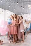 Tres hermanas más jovenes que abrazan a su hermana de anticipación imagenes de archivo