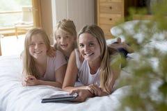 Tres hermanas que usan una tableta digital en casa Imagenes de archivo
