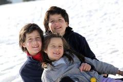 Tres hermanos en la nieve en las montañas en invierno fotos de archivo