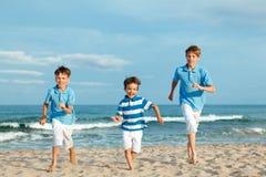 Tres hermanos están corriendo en la playa Foto de archivo libre de regalías