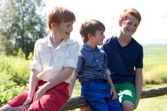 Tres hermanos felices que se sientan en la cerca Fotografía de archivo libre de regalías