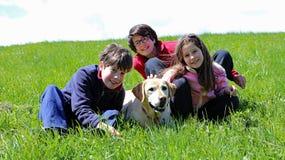 Tres hermanos jovenes dos muchachos y una muchacha con el labrador retriever Foto de archivo libre de regalías
