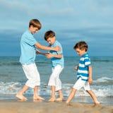 Tres hermanos son juego en la playa Imagenes de archivo