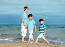 Tres hermanos son juego en la playa Imágenes de archivo libres de regalías