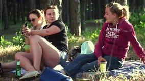 Tres hermosos, chicas j?venes que se sientan en la colcha, en la tierra en vaqueros, camiseta, pantalones cortos, traje, zapatill almacen de video