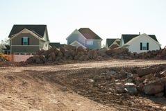 Tres hogares nuevamente construidos rodeados por los escombros fotos de archivo libres de regalías