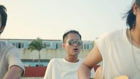 Tres hombres adultos asiáticos jovenes que cantan tocando la guitarra metrajes