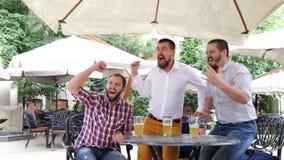 Tres hombres con la cerveza en café al aire libre que miran deporte almacen de video
