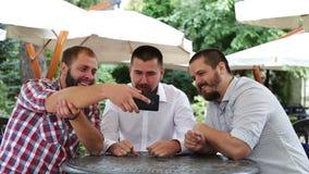 Tres hombres con las barbas que beben la cerveza ligera, hablando metrajes