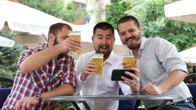 Tres hombres con las barbas que se sientan en el café, cerveza de consumición almacen de metraje de vídeo