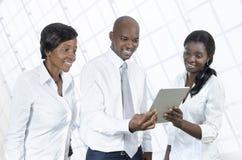 Tres hombres de negocios africanos con la tableta Imagen de archivo libre de regalías