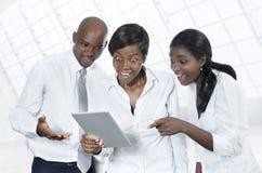 Tres hombres de negocios africanos con la tableta Imágenes de archivo libres de regalías