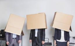Tres hombres de negocios con las cajas sobre sus cabezas en una oficina Imágenes de archivo libres de regalías