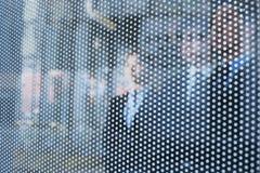 Tres hombres de negocios detrás de una pared de cristal que mira hacia fuera, caras irreconocibles Imagen de archivo