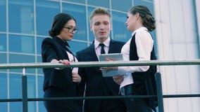 Tres hombres de negocios: dos mujeres y hombre que hablan de su cooperación futura metrajes