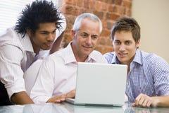 Tres hombres de negocios en la oficina que mira la computadora portátil Imagen de archivo libre de regalías