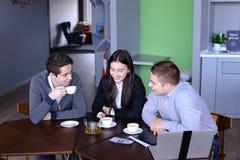 Tres hombres de negocios, mujer y hombres discutiendo el robot con la taza de te imagen de archivo
