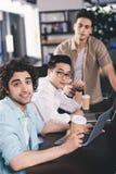 tres hombres de negocios multiétnicos con las tazas de café del papel que se sientan en la tabla con los ordenadores portátiles e imágenes de archivo libres de regalías