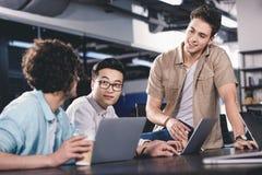tres hombres de negocios multiculturales que tienen reunión con las tazas de café de papel en la tabla con los ordenadores portát imagenes de archivo