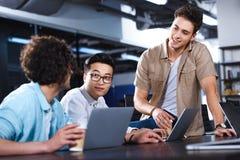 tres hombres de negocios multiculturales que tienen reunión con las tazas de café de papel en la tabla con los ordenadores portát imagen de archivo libre de regalías