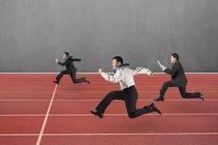 Tres hombres de negocios que corren en pista roja Imágenes de archivo libres de regalías