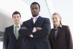 Tres hombres de negocios que defienden al aire libre el buildin Imagen de archivo