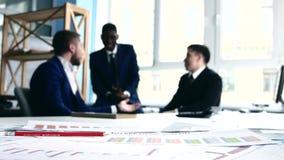 Tres hombres de negocios que discuten las ideas, discutiendo metrajes