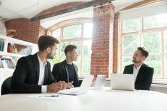 Tres hombres de negocios que negocian discutiendo negocio en la conferencia foto de archivo