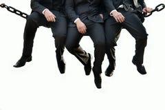 Tres hombres de negocios que se sientan en la cerca Imagen de archivo libre de regalías