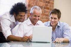 Tres hombres de negocios que se sientan en oficina con la computadora portátil Imágenes de archivo libres de regalías