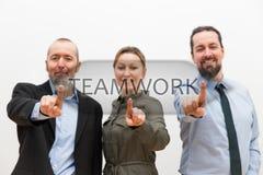 Tres hombres de negocios que tocan un botón virtual foto de archivo libre de regalías
