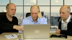 Tres hombres de negocios se sientan en la tabla con el ordenador portátil y discuten proyecto Oficina moderna con las ventanas y  metrajes