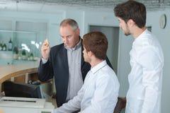 Tres hombres detrás del mostrador de recepción fotos de archivo libres de regalías