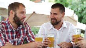 Tres hombres en café que beben la cerveza ligera, hablando almacen de video
