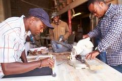 Tres hombres en el trabajo en un taller de la carpintería, Suráfrica Foto de archivo libre de regalías