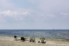 Tres hombres en la playa en el fondo del mar imagen de archivo