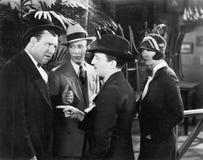 Tres hombres en una discusión mientras que una mujer que mira encendido (todas las personas representadas no son vivas más largo  Imagen de archivo libre de regalías