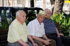 Tres hombres españoles que se sientan en banco. Fotos de archivo