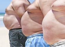 Tres hombres gordos en una playa Fotos de archivo libres de regalías