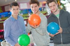 Tres hombres jovenes con la bola de bolos imagenes de archivo
