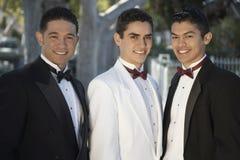 Tres hombres jovenes en los smokinges que se unen en Quinceanera Fotografía de archivo