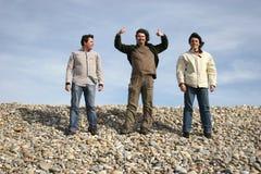 Tres hombres jovenes ocasionales en la playa Imágenes de archivo libres de regalías
