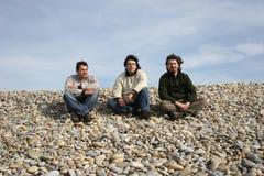 Tres hombres jovenes ocasionales en la playa Foto de archivo