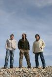 Tres hombres jovenes ocasionales en la playa imagen de archivo