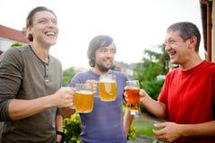 Tres hombres jovenes pasan alegre tiempo detrás de un vidrio de cerveza Imagen de archivo