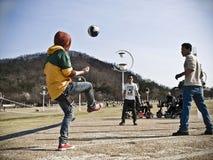 Tres hombres jovenes que juegan a fútbol en un parque coreano Foto de archivo