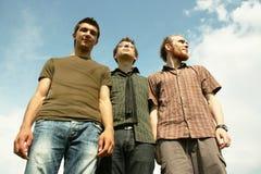 Tres hombres jovenes que se colocan al aire libre Foto de archivo