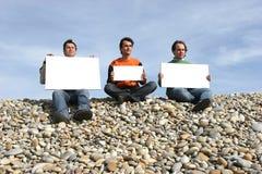 Tres hombres jovenes que sostienen las tarjetas blancas Imagen de archivo