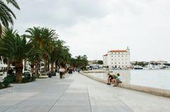 Tres hombres jovenes se sientan en la 'promenade' del mar adriático, se relajan y hablan Imágenes de archivo libres de regalías